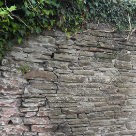 Traditional stone wall showing cracks and damage